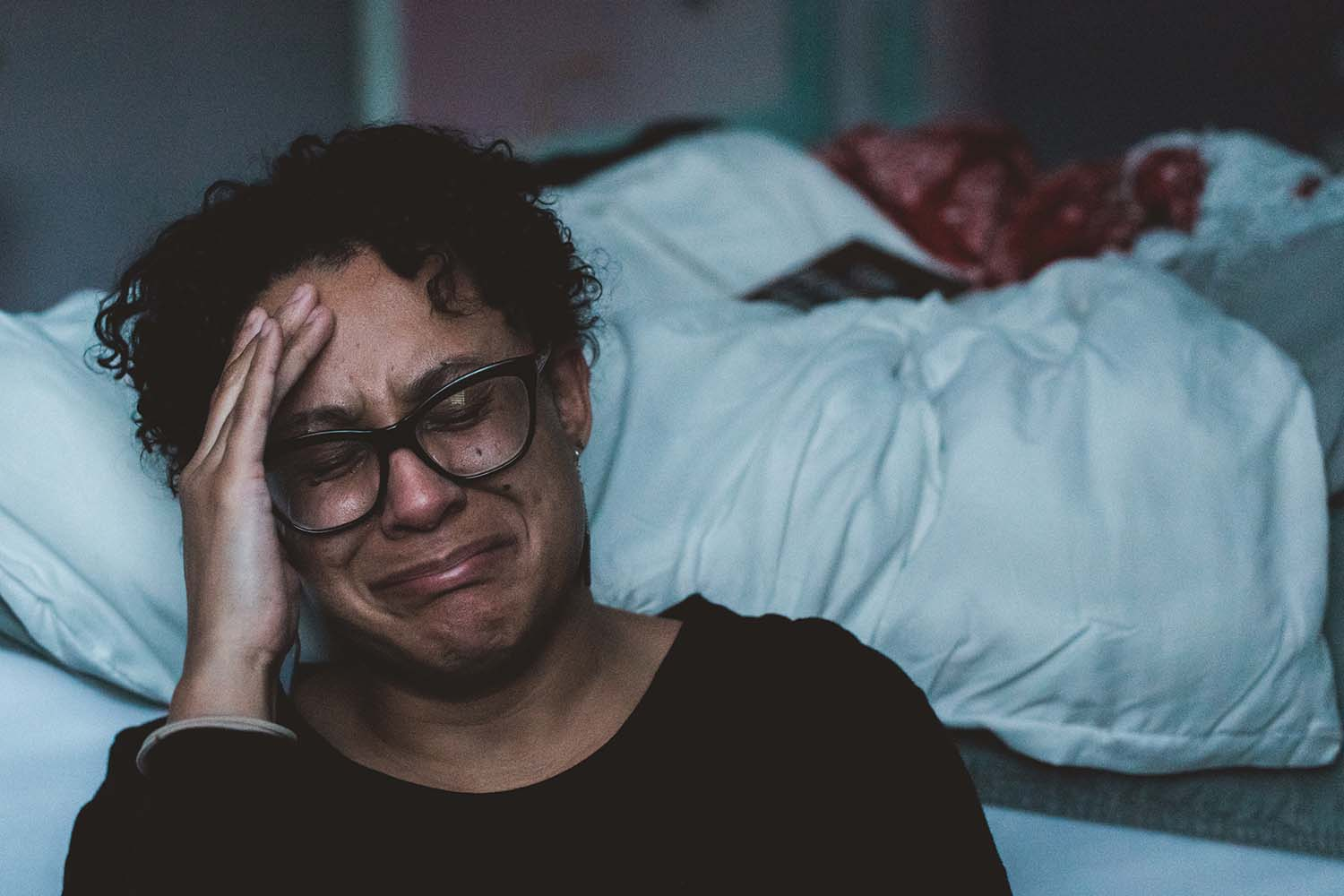 A mother crying in her bedroom
